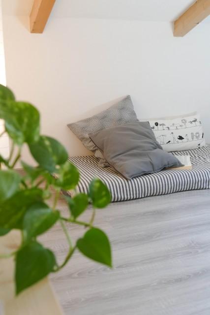 angolo lettura in mansarda creato con un materasso e dei cuscini