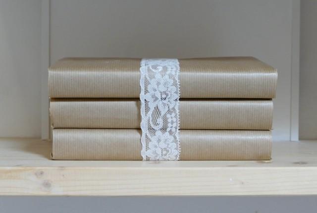 libri ricoperti di carta da pacco con nastro in pizzo come elemento di decoro