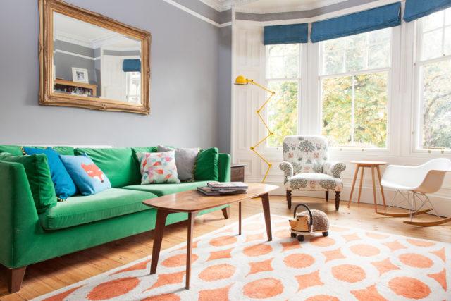 un living pieno di colore grazie al divano verde Ikea al tappeto cuscini a fantasia