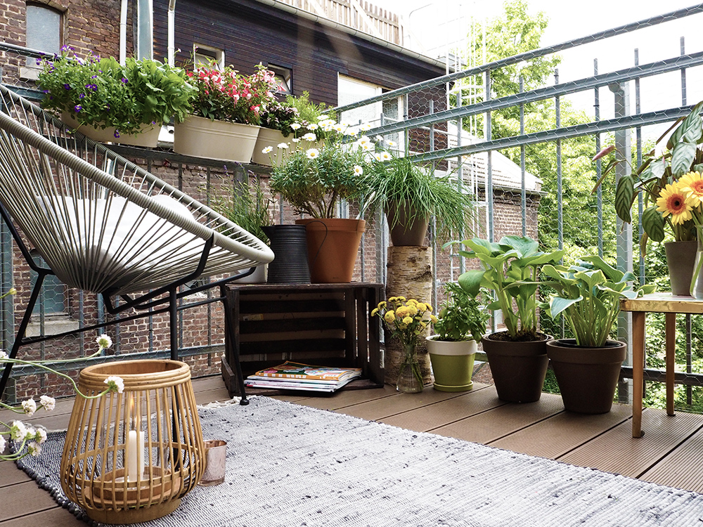 dettaglio del balcone con tappeto lanterne piante e seduta