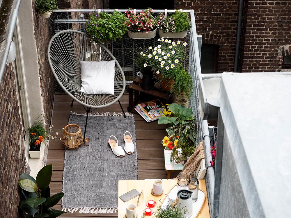 come decorare il balcone con un tappeto, una seduta comoda e i fiori
