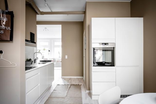 cucina bianca in contrasto con parete toni del marrone