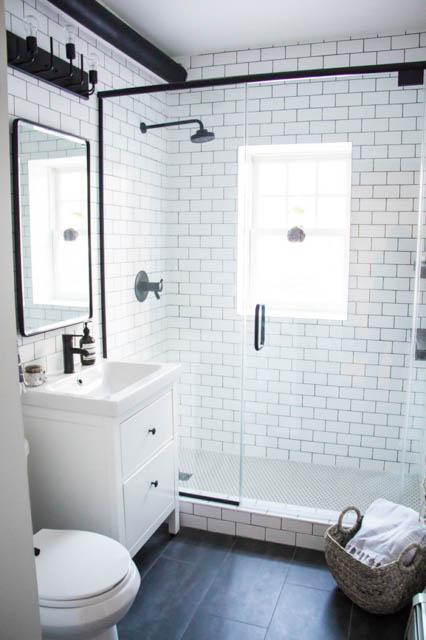 tendenza bagno stile scandinavo rubinetteria nera e cesto in materiali naturali sul pavimento come porta asciugamani