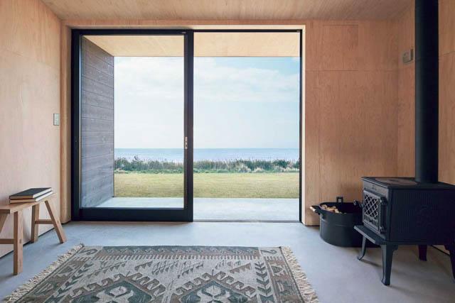 una sola stanza con una grande vetrata in questa minimal home prefabbricata c
