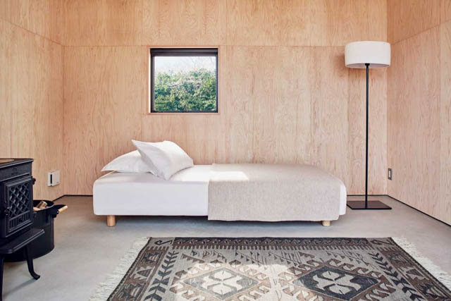 una sola stanza con un letto e una stufa in questa minimal home prefabbricata c