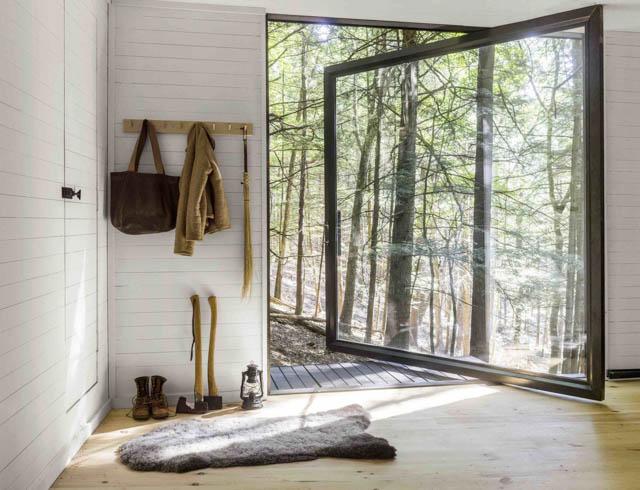 una grande vetrata e tanto legno in questa minimal home nel bosco