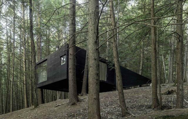 una minimal home di legno costruita nel bosco