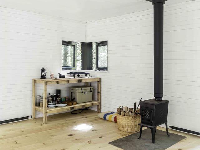 cucina con stufa a legna in una minimal home nel bosco