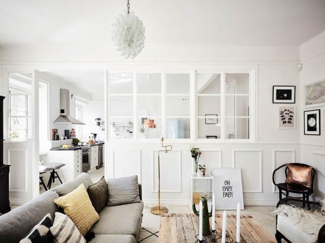 una divisione luminosa della cucina dal soggiorno grazie ad una parete divisoria in vetro bianca