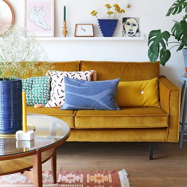divano color senape in velluto con cuscini