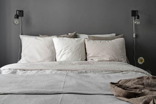 letto con biancheria in lino dai colori neutri e applique nere