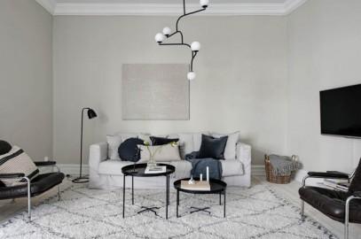 soggiorno con divano chiaro pareti neutre e lampadario di design