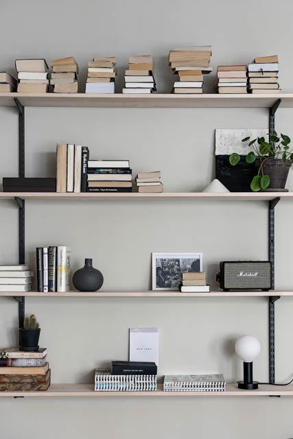 mensole con libri e parete tono neutro