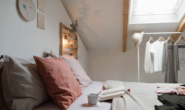 camera da letto con elementi di decoro e rella bianca con abiti