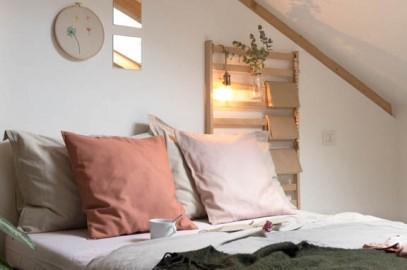 cuscini rosa antico e ruggine sul letto della camera mansardata