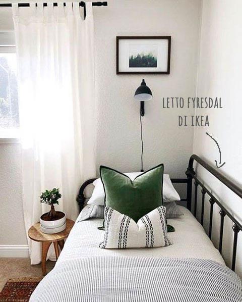 camera ospiti con letto con lenzuola a righe e cuscino verde