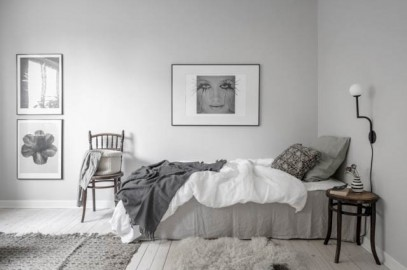 letto singolo con lenzuola grigie e poster alle pareti